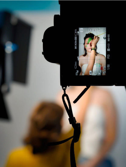 Camera viewfinder showing model getting ready for photo shoot