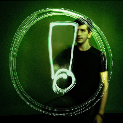 Man drawing exclamation mark in circle with green light