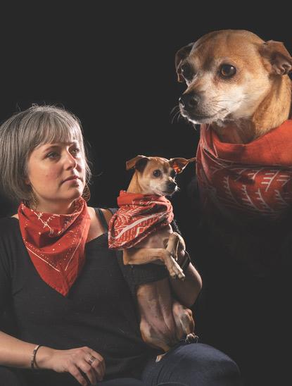 Woman holding small dog both wearing bandanas