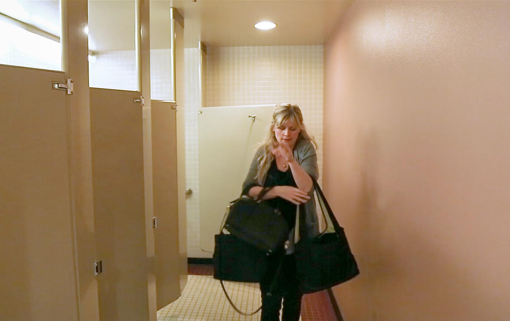 Mom leaving bathroom after pumping breast milk