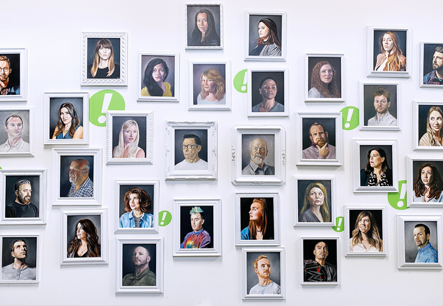 Wall displaying portraits of many of WONGDOODY's employees