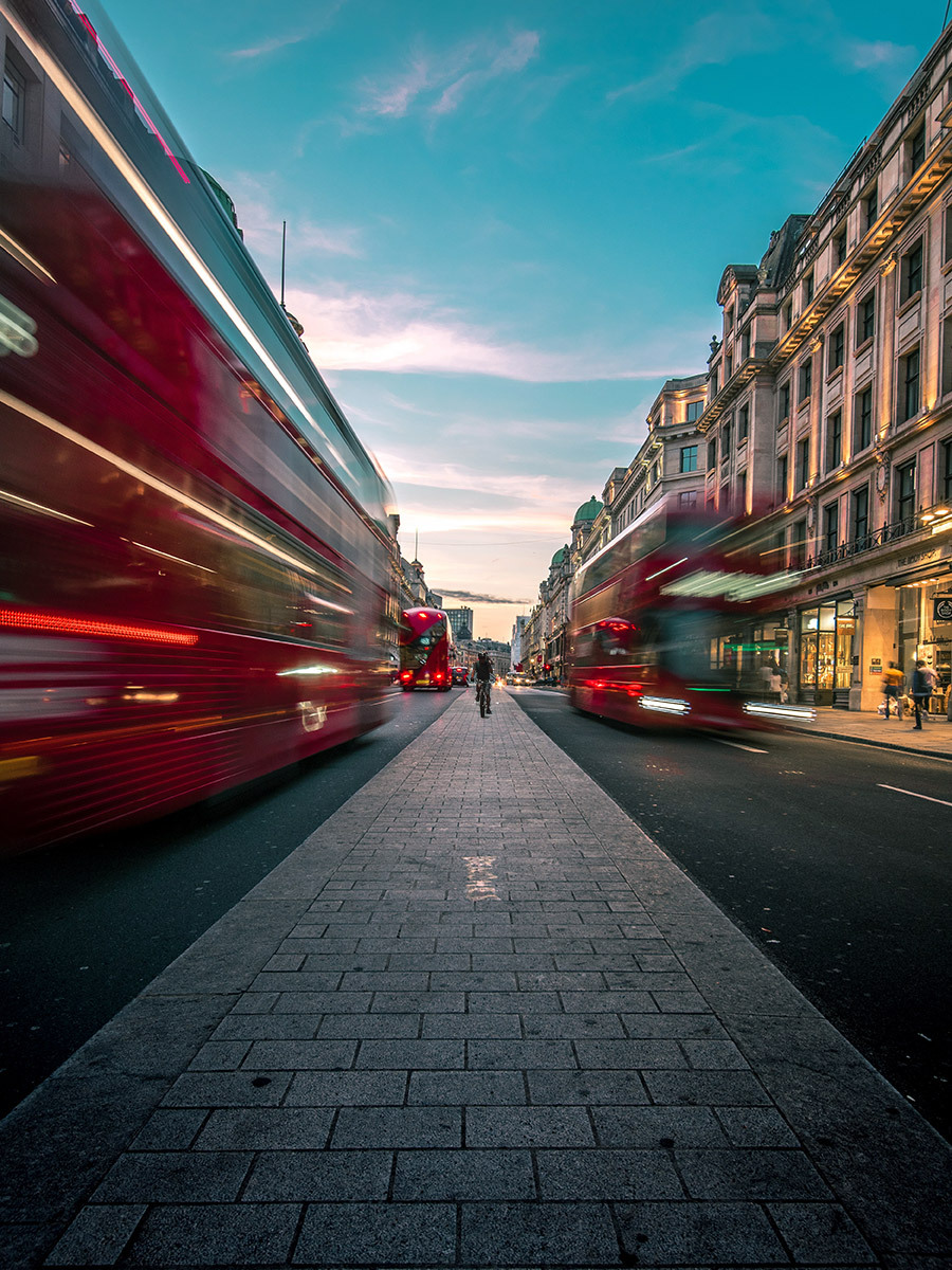 Busy street in the UK with red buses